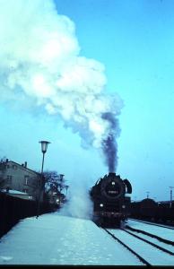 Der Interzonenzug von Hamburg nach Dresden fährt im verschneiten Bahnhof Büchen mit gewaltiger Dampfwolke an